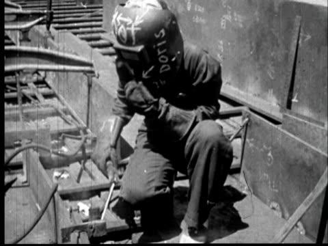 1945 ms worker welding/ woman lifting mask and wiping sweat from face/ sylacauga, alabama - 女性の権利点の映像素材/bロール