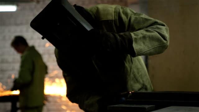 vídeos de stock, filmes e b-roll de trabalhador soldas emendas sobre a peça de metal. - soldar