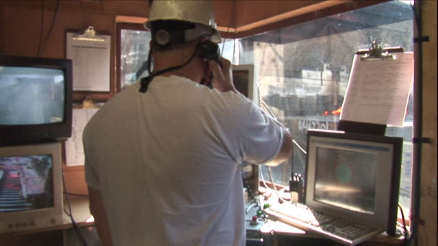 a worker with a hard hat works from a steel factory control room. - control room stock videos & royalty-free footage