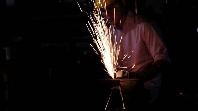 vidéos et rushes de travailleur avec meuleuse d'angle soudage et de coupage. - en métal