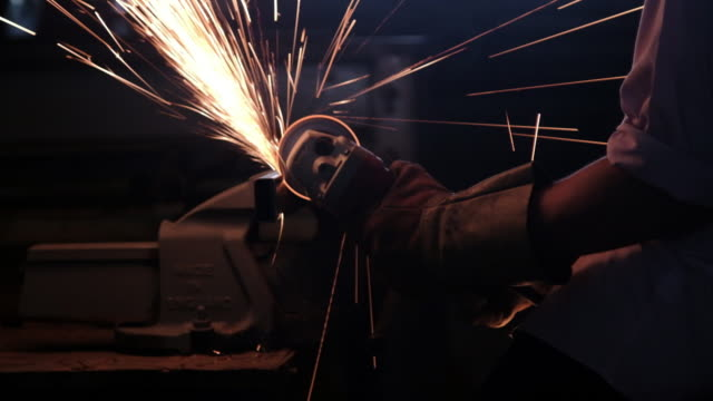 Worker with Angle Grinder welding and cutting.