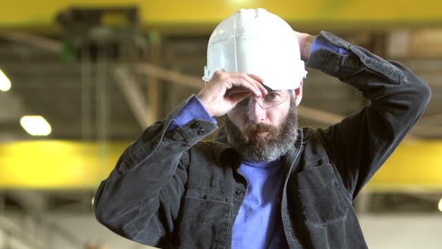 worker with beard standing in warehouse - work helmet stock videos & royalty-free footage