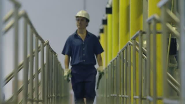 vídeos y material grabado en eventos de stock de ls rf worker with clip walking to camera, red r3d 4k - casco herramientas profesionales