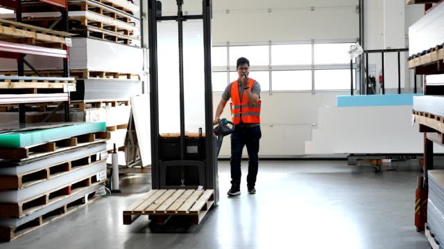 arbeiter mit maschinen im gespräch auf walkie-talkie - hubwagen stock-videos und b-roll-filmmaterial