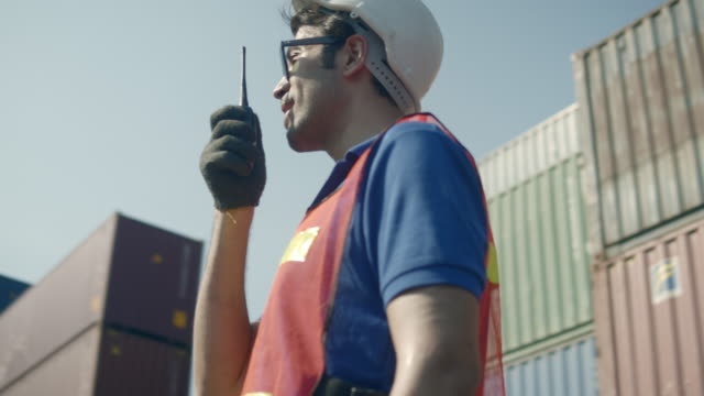 worker with walkie talkie and safety equipment on shipping port - 360 stock videos & royalty-free footage