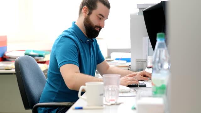 vidéos et rushes de ouvrier travaillant au bureau d'ordinateur en atelier d'impression - un seul homme d'âge moyen