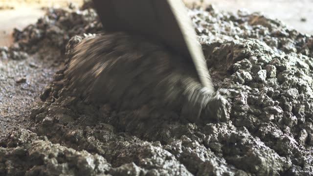 arbeiter, der für das mischen von zement auf bodenweise im bau arbeitet. - ausbreiten stock-videos und b-roll-filmmaterial