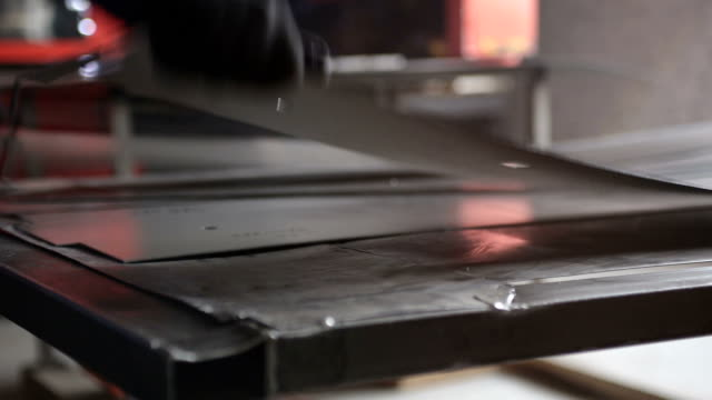 worker works with a metal sheet at the factory. - sheet metal stock videos and b-roll footage