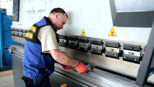 stockvideo's en b-roll-footage met werknemer werkt met een pers voor het verwerken van metalen knuppels. - productielijn werker