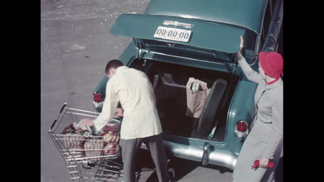 ms workerputting shopping bags on car trunk for woman / united states - shopping trolley stock videos and b-roll footage