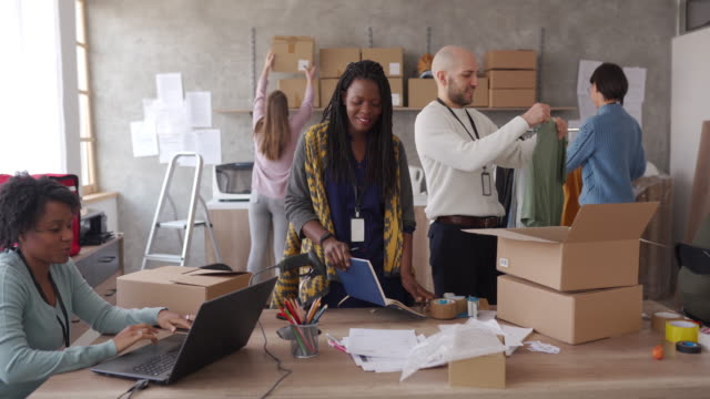 workers accepting new orders online and packing merchandise for customers - clothes shop stock videos & royalty-free footage