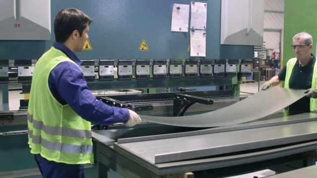 Workers adjusting metal sheet on press machine