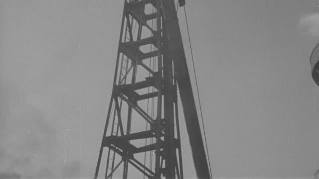 vidéos et rushes de 1946 montage workers and crane operator raising a pile at construction site / united kingdom† - 1946