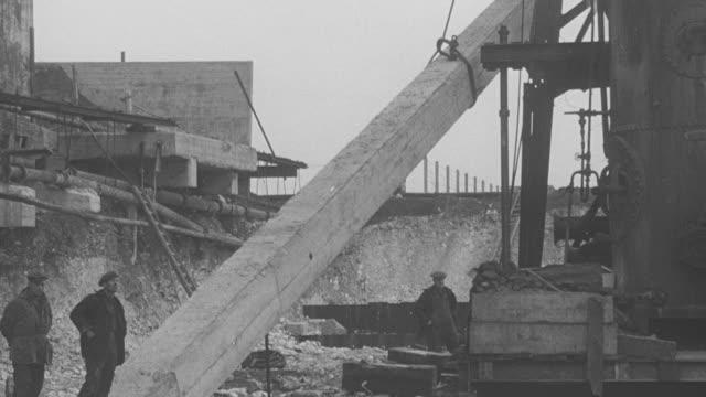 vidéos et rushes de 1946 tu workers and crane raising a pile at construction site / united kingdom† - 1946