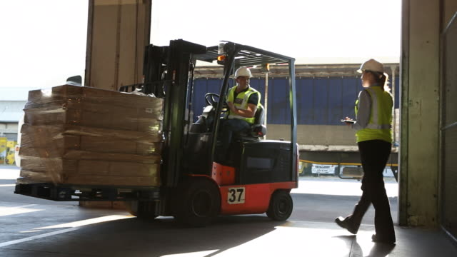 vidéos et rushes de workers and machinery in a large food distribution warehouse - décharger