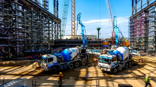 workers and truck directing or pouring concrete onto structure of the power plant construction site - safety stock videos & royalty-free footage