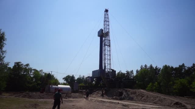 Workers approach the derrick of a drilling rig during gas extraction operations by DK Ukrgazvydobuvannya a unit of NAK Naftogaz Ukrainy in Poltava...