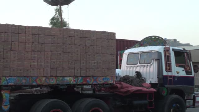 Workers are seen stacking boxes of tiles on a truck at the Shabbir Tiles Ceramics Ltd production facility at dusk in Karachi Pakistan on Wednesday...