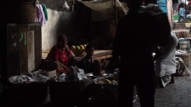 workers are silhouetted as they walk past vendors waiting for customers at a market in the howrah area of kolkata, india, on friday, may 26 vendors... - kolkata stock videos & royalty-free footage