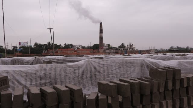workers are trying to save bricks from rainy weather by covering polythene in brick field in savar dhaka - savar stock videos and b-roll footage