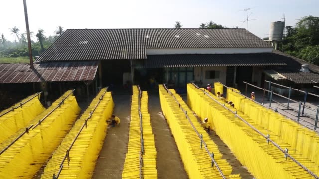 workers arrange racks of noodles to dry in the sun at the tiantiamhenghuat noodle factory in the ban pong district of ratchaburi province thailand on... - drying rack stock videos and b-roll footage