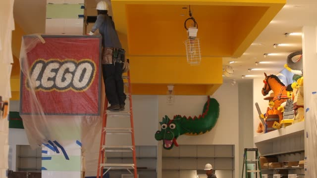 Workers assemble a Lego sculpture in the new Lego store set to open in the Flatiron District in New York NY US Workers assemble a Lego logo made of...