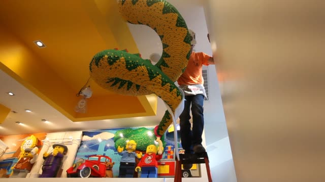 Workers assemble a Lego sculpture modeled after the Statue of Liberty in the new Lego store set to open in the Flatiron District in New York NY US...