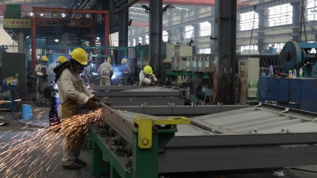 Workers assemble a shipping container in the welding shop at the SingamasContainer Holdings Ltd factory in Qidong China on Thursday June 22 2017