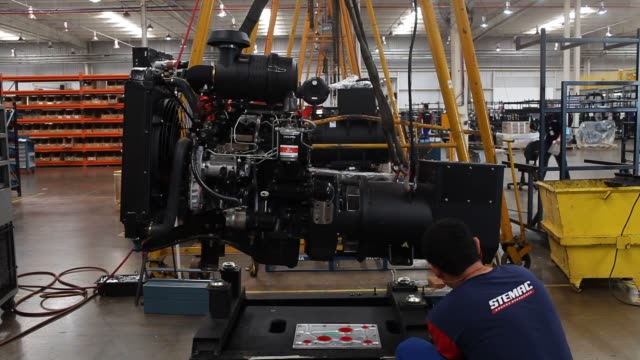 workers assemble electrical generators at the new facility of stemac in itumbiara brazil wednesday april 29 2015 shots an employee guides an electric... - generatore elettrico video stock e b–roll