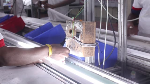 workers assemble e-lite led 18 w pride plus lights on the production line of the light-emitting diode fixture assembly unit at the havells india ltd.... - led light stock videos & royalty-free footage