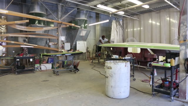 Workers assemble parts of the wooden interior of Chris-Craft