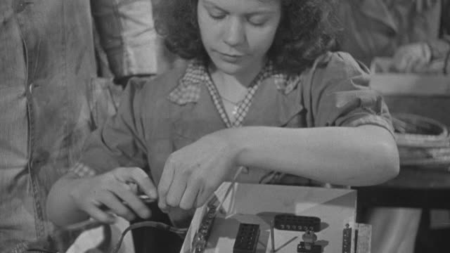 1947 montage workers assembling and testing electrical equipment and wiring for prefabricated airey houses, and boxes containing them moving down a conveyor belt / united kingdom - electrical component stock videos & royalty-free footage