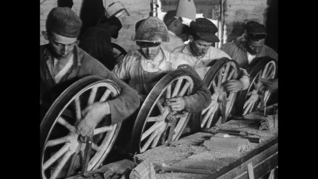 Workers assembling cars putting spokes on wheels rims