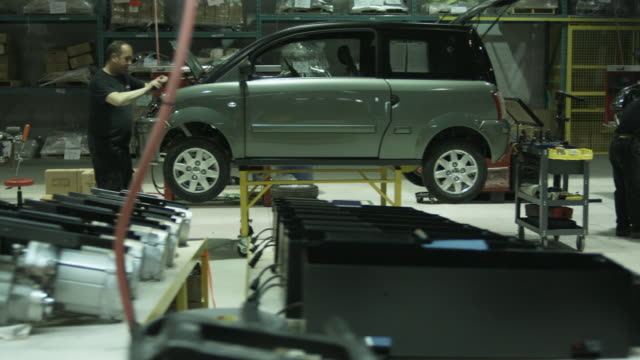 ws pan workers assembling electric car on assembly line, st. jerome, quebec, canada - 自動車産業点の映像素材/bロール
