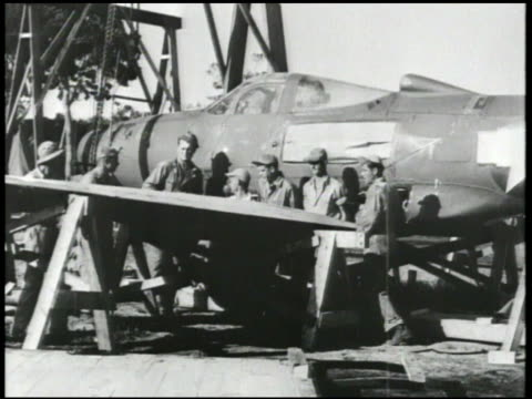 S workers assembling wing to fighter aircraft fuselage attaching tail rudder machine gun turrets engine propeller World War II WWII war production...