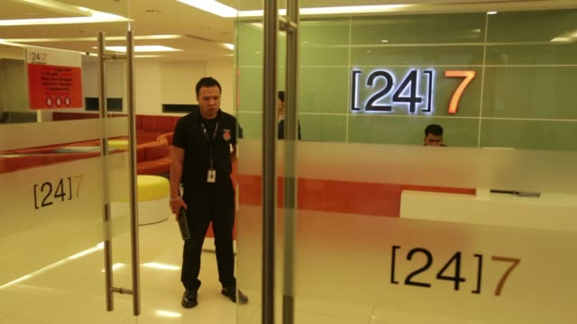 workers at 24/7 call center in cebu, philippines on sep 26, 2015 shots shot of the call center logo behind the desk, wider shot of entrance as people... - outsourcing stock videos & royalty-free footage