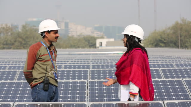 Workers at a 1 MW solar power station run by Tata