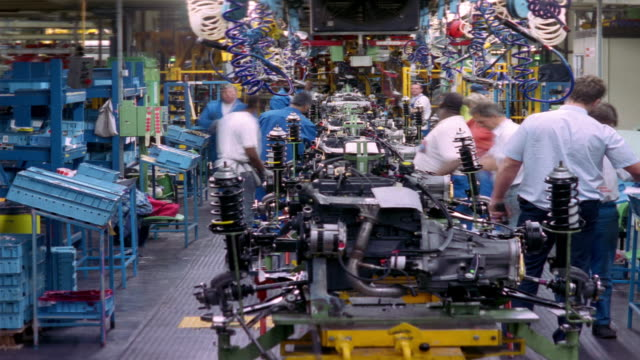 t/l, ms, workers at car engine assembly line, dagenham, england - automobile industry video stock e b–roll