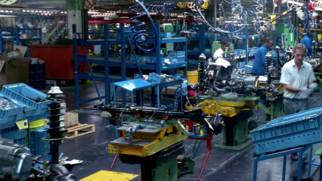 t/l, ms, workers at car engine assembly line, dagenham, england - inghilterra video stock e b–roll