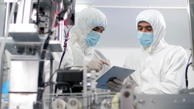 lavoratori della fabbrica di attrezzature mediche - controllo video stock e b–roll