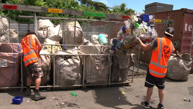 Workers at recycling centre emptying cages and bins of plastic bottles into canvas bins