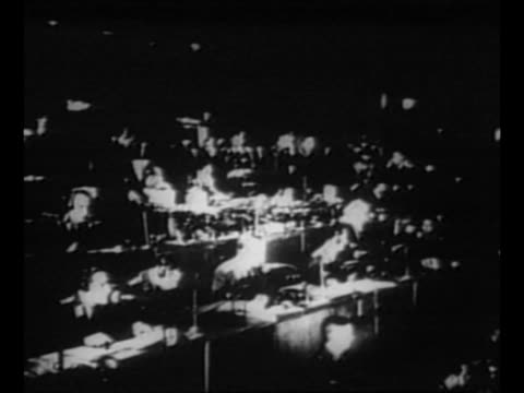 ws workers at tables at nazi air raid warning center during world war ii / men and women make notations on lighted map / shadow of workers... - bomber stock-videos und b-roll-filmmaterial