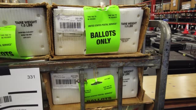 vídeos y material grabado en eventos de stock de workers at the miami-dade county election department move racks of vote-by-mail ballots onto a u.s. post office truck to be delivered to voters on... - condado de miami dade