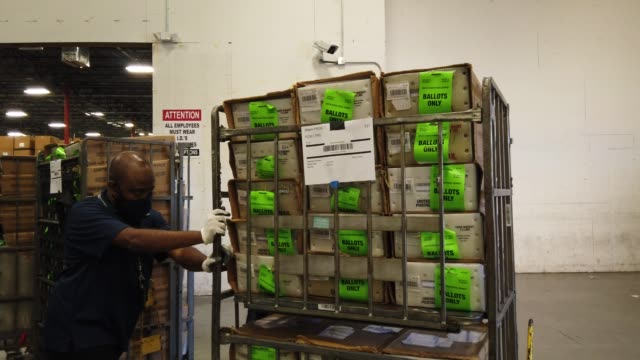 workers at the miami-dade county election department move racks of vote-by-mail ballots onto a u.s. post office truck to be delivered to voters on... - miami dade county stock videos & royalty-free footage
