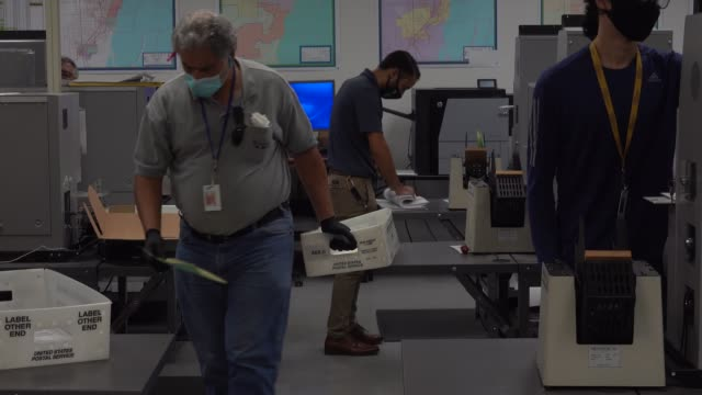 vídeos y material grabado en eventos de stock de workers at the miami-dade county elections department work on tabulating the vote by mail ballots that have been returned for the general election on... - condado de miami dade
