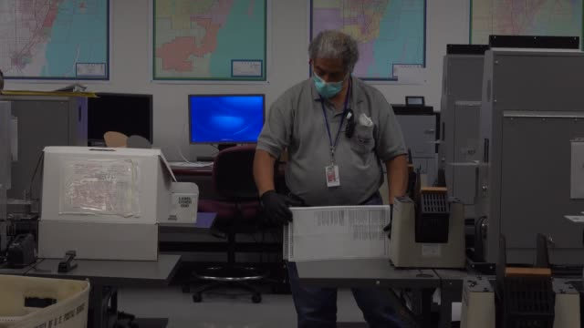 workers at the miami-dade county elections department work on tabulating the vote by mail ballots that have been returned for the general election on... - miami dade county stock videos & royalty-free footage