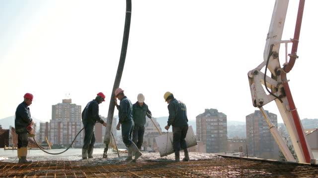 stockvideo's en b-roll-footage met werknemers op de top van het gebouw beton gieten - ingenieurswerk
