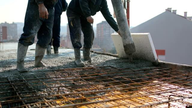 Arbeiter an der Spitze des Gebäudes Beton gießen