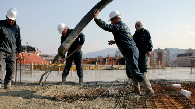 workers at the top of the building pouring concrete - imbracatura di sicurezza video stock e b–roll