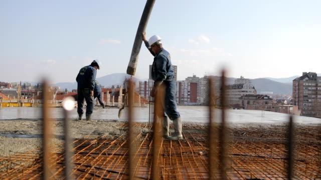 Werknemers op de top van het gebouw beton gieten